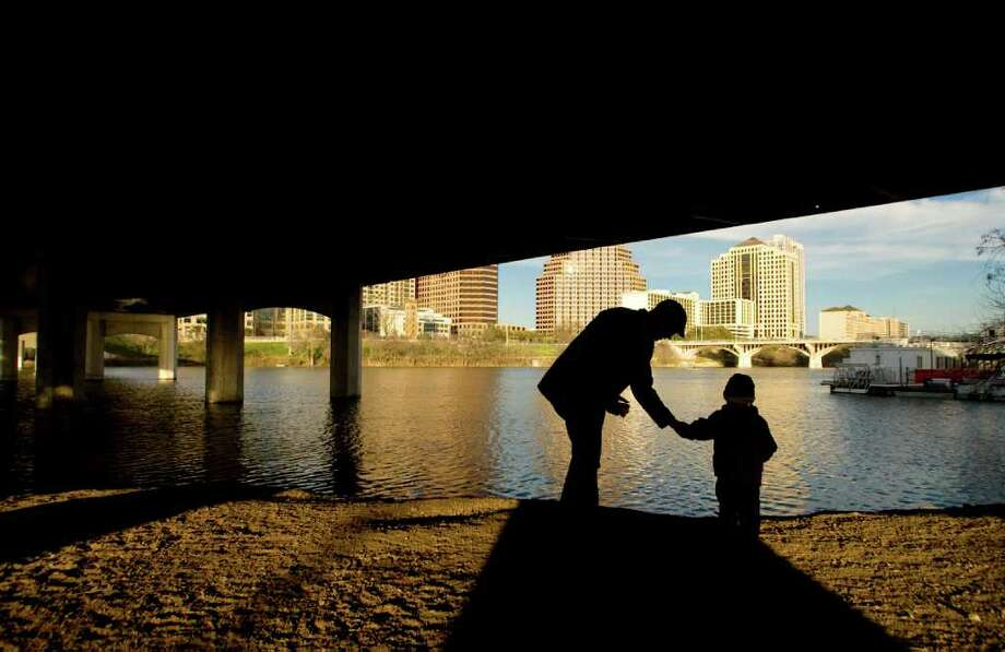 Jarid Craig and his 3-year-old son Finnegan Craig spend some quality time together under the First Street Bridge at Auditorium Shores throwing rocks into the water on Tuesday Feb. 9, 2010. Photo: Jay Janner / Austin American-Statesman