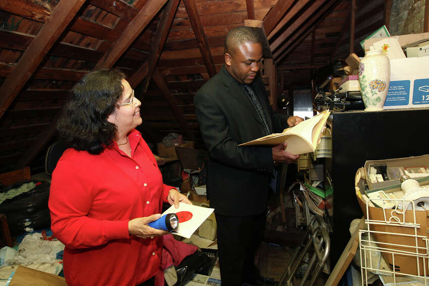 Trinity University Project Archivist Donna Guerra (left) and Taj Matthews look over papers in the Rev. Claude Black Jr.'s attic at Black's home on Wyoming Street on Wednesday, Feb. 29, 2012. Black died in 2009, and Matthews, Black's grandson, is donating the collection Trinity University.