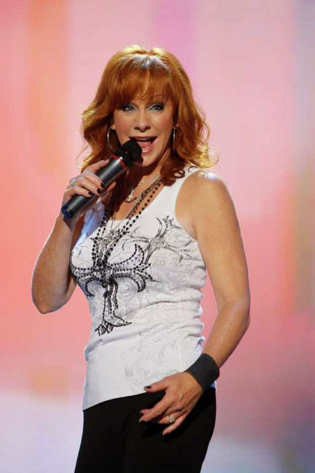 SIMPLICITY: Reba McEntire performs during the CMA Music Festival in Nashville with just a T-shirt and jeans, but she does it with flair. Photo: Wade Payne / FR23601 AP