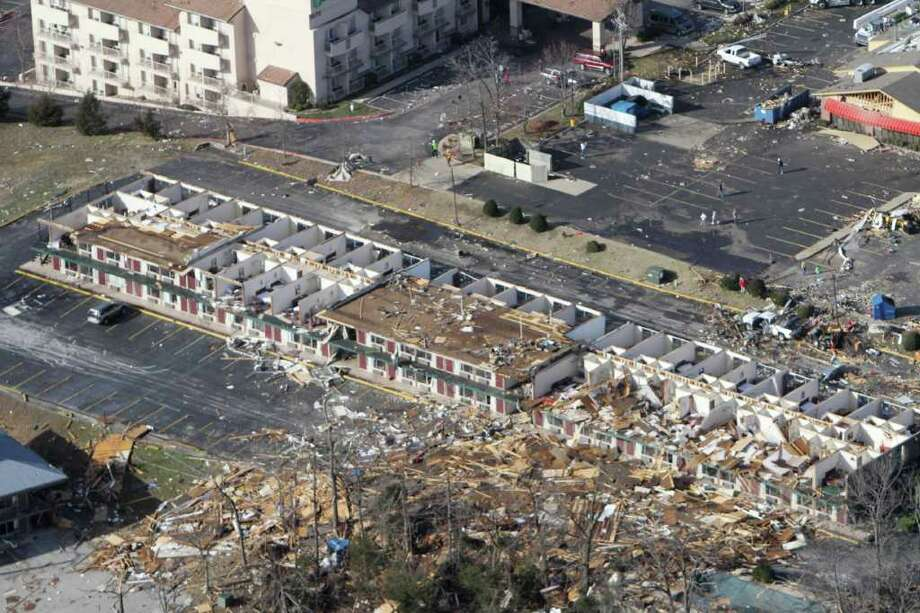 Debris from a storm-damaged motel is blown across the parking lot Wednesday, Feb. 29, 2012, in Branson, Mo. A powerful storm system that produced multiple reports of tornadoes lashed the Midwest early Wednesday, roughing up the entertainment resort town of Branson and laying waste to small towns in Illinois and Kansas. At least nine people were killed. (AP Photo/The News-Leader, Dean Curtis) NO SALES Photo: AP