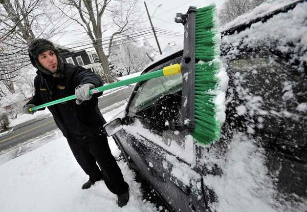 Jonathan Farrell clears his car of snow in his father's driveway along Westville Avenue in Danbury on Wednesday, Feb. 29, 2012. Photo: Jason Rearick / The News-Times