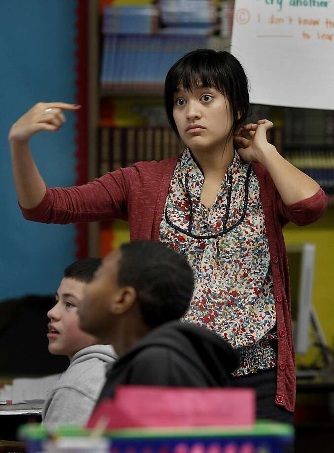 Teacher Kat Florita signals a student to enter the classroom. Kat Florita teaches an 8th grade language arts class at Everett Middle School in San Francisco, Calif.  She is one of the first year teachers who will not get a layoff notice because she is in the Superintendent's Zone, a specially skilled and trained instructor. Photo: Brant Ward, The Chronicle