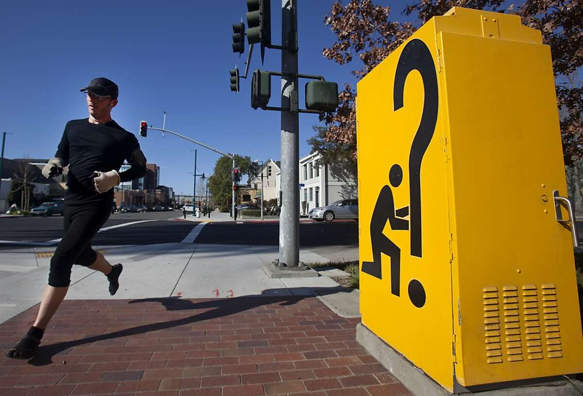 """A jogger runs past a """"Signs of the Times"""" electrical box on Park Avenue on Saturday morning in Emeryville. Emeryville's Art in Public Places program features sculptures by local artists that are scattered throughout the city. Pieces like """"Signs of the Times,"""" sit on street corners, local businesses, and parks."""