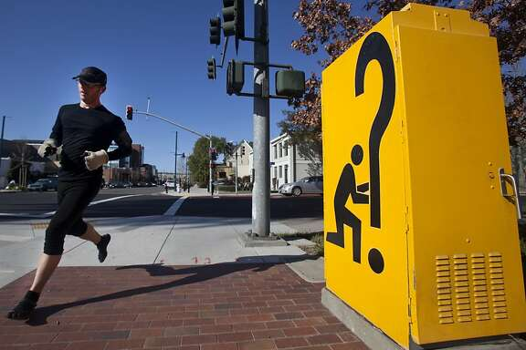 "A jogger runs past a ""Signs of the Times"" electrical box on Park Avenue on Saturday morning in Emeryville. Emeryville's Art in Public Places program features sculptures by local artists that are scattered throughout the city. Pieces like ""Signs of the Times,"" sit on street corners, local businesses, and parks."