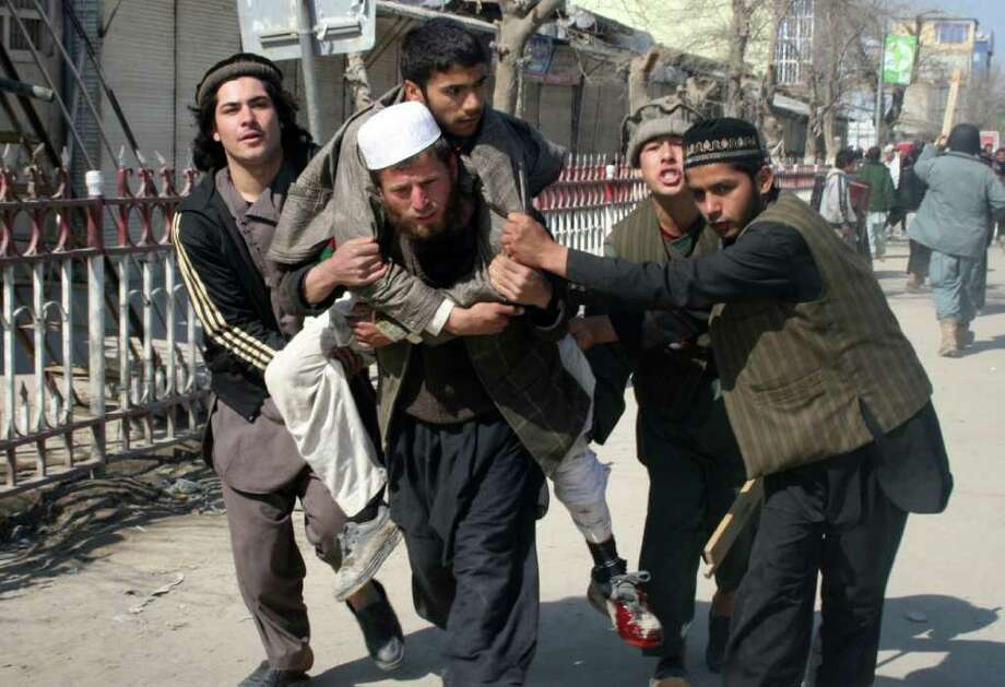 Afghans carry a man who was wounded during an anti-U.S. demonstration in Kunduz, Afghanistan, on Saturday. Photo: Ezatullah Pamir / AP