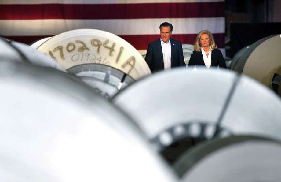 Republican presidential candidate, former Massachusetts Gov. Mitt Romney and his wife Ann walk past rolls of sheet metal as they arrive at a campaign rally at American Posts in Toledo, Ohio, Wednesday, Feb. 29, 2012. (AP Photo/Gerald Herbert) Photo: Gerald Herbert, Associated Press / AP