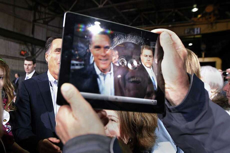 A supporter's reflection and the image of Republican presidential candidate, former Massachusetts Gov. Mitt Romney, are seen on the screen of his iPad as he photographs Romney, greeting supporters at American Posts in Toledo, Ohio, Wednesday, Feb. 29, 2012. (AP Photo/Gerald Herbert) Photo: Gerald Herbert, Associated Press / AP