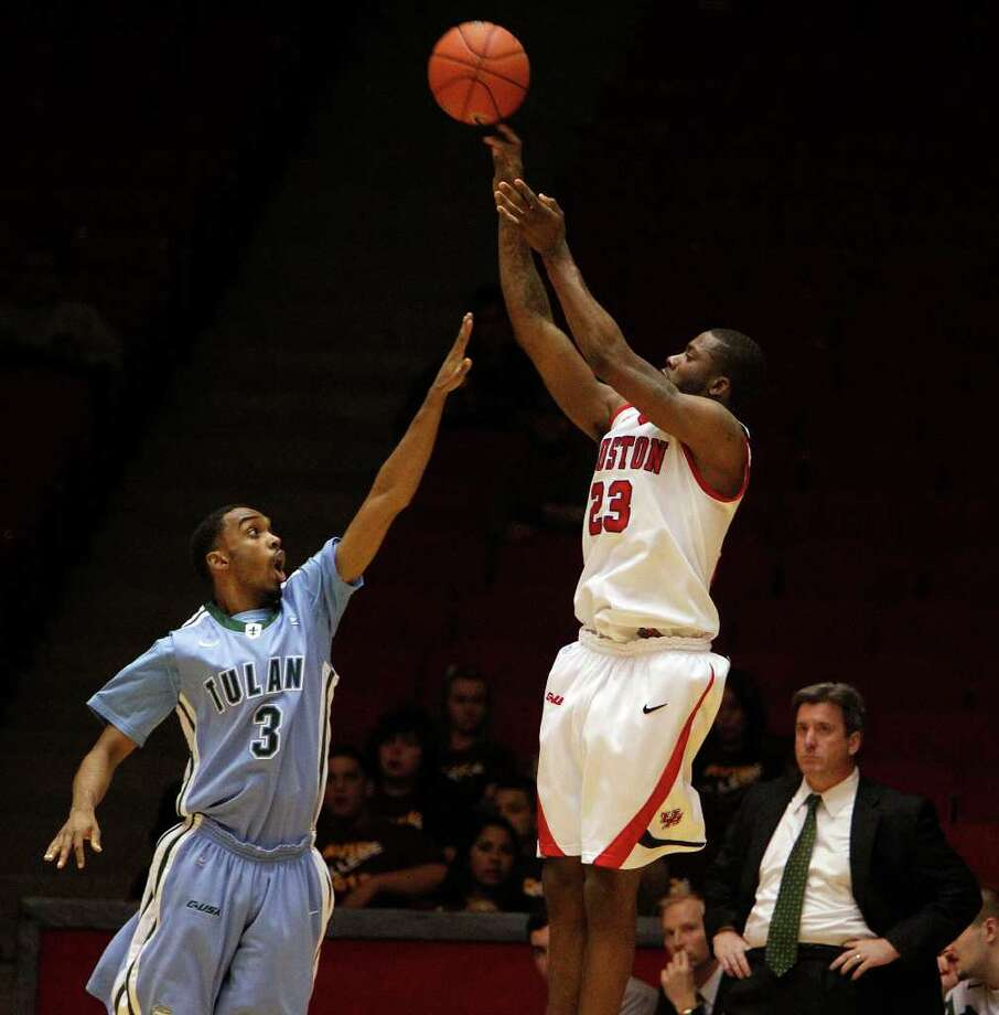 The University of Houston's Jonathon Simmons center, shoots the ball over Tulane University's Trent Rogers left, as Tulane's head coach Ed Conroy right, looks on during the first half of men's college basketball game action at the University of Houston's Hofheinz Pavilion Wednesday, Feb. 29, 2012, in Houston. Photo: James Nielsen, Chronicle / © 2011 Houston Chronicle