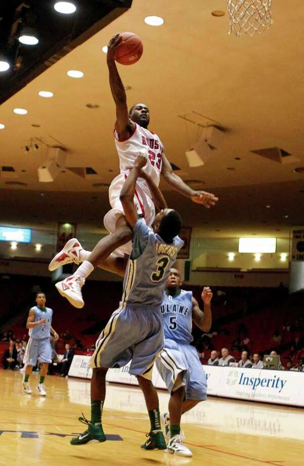 The University of Houston's Jonathon Simmons left, slam dunks over Tulane University's Trent Rogers during the second half of men's college basketball game action at the University of Houston's Hofheinz Pavilion Wednesday, Feb. 29, 2012, in Houston. Photo: James Nielsen, Chronicle / © 2011 Houston Chronicle
