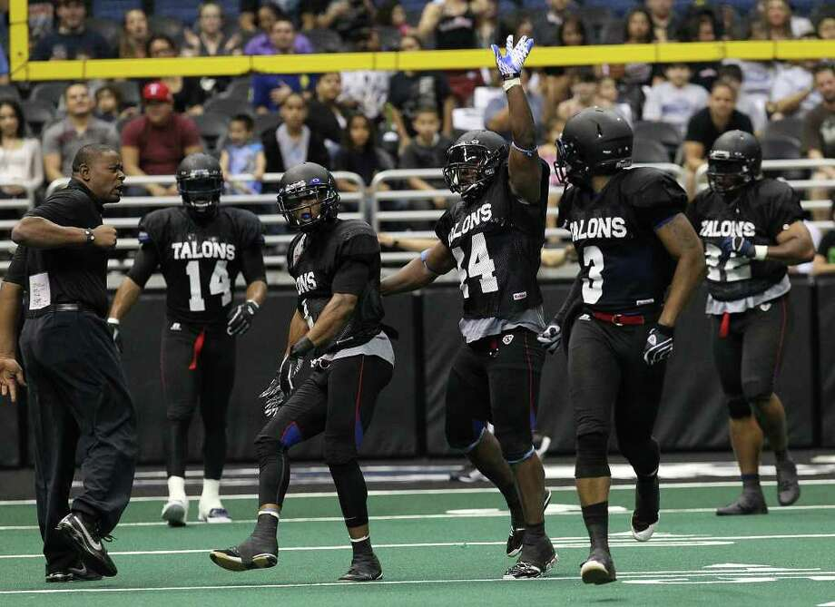 San Antonio Talons' coach Lee Johnson (left) celebrates with players Kenneth Fonterette, Jr (second from left), Jamar Ransom (44) and Fred Show (03) after making a defensive stop against San Jose SaberCats in an exhibition game for the city's newest American Football League team at the Alamodome on Wednesday, Feb. 29, 2012. The Talons first game will be on March 10. Photo: Kin Man Hui, Kin Man Hui/San Antonio Express-News / San Antonio Express-News
