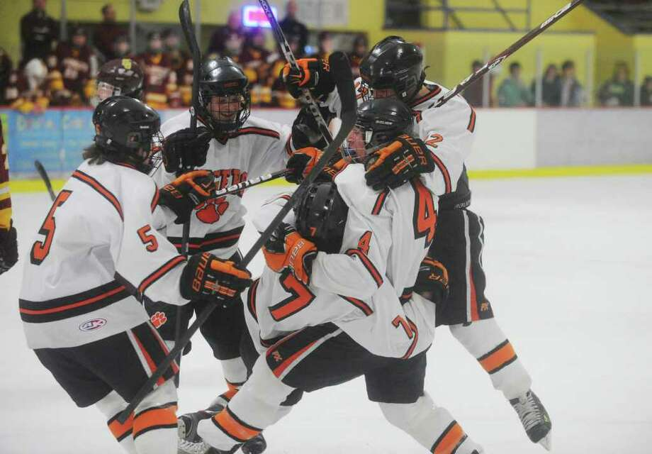 The Ridgefield Tigers pile onto Christopher Morrow, jersey number 7, after his first period goal as St. Joseph and Ridgefield High Schools face off in the FCIAC boys hockey semifinals at Terry Conners Rink in Stamford, Conn., February 29, 2012. Photo: Keelin Daly / Stamford Advocate
