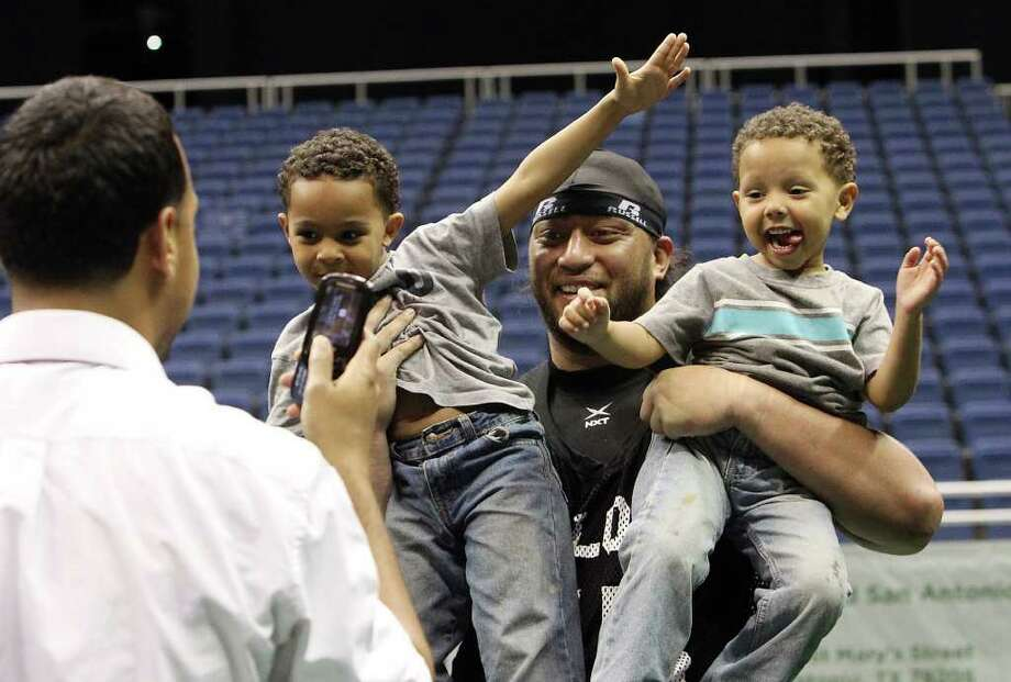 San Antonio Talons' Simi Toedina (55) holds onto siblings Wyatt (second from left) and Ryan Garcia as their father Matthew (left) takes a picture of his boys with the player after the Talons exhibition game against San Jose SaberCats at the Alamodome on Wednesday, Feb. 29, 2012. The Talons first game will be on March 10. Photo: Kin Man Hui, Kin Man Hui/San Antonio Express-News / San Antonio Express-News