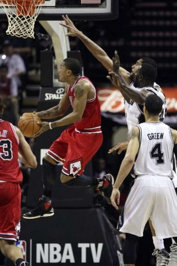 SPURS --  Chicago Bulls Derrick Rose drives to the basket past San Antonio Spurs Tim Duncan and DeJuan Blair during the first half at the AT&T Center, Wednesday, Feb. 29, 2012. Jerry Lara/San Antonio Express-News (San Antonio Express-News)