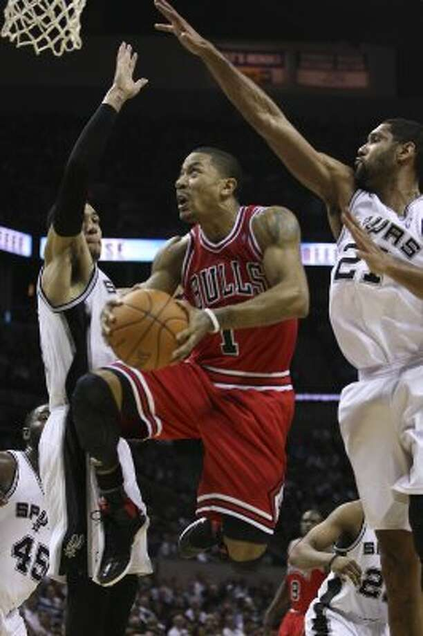 SPURS --  Chicago Bulls Derrick Rose cuts through the defense of San Antonio Spurs Danny Green, left, and Tim Duncan during the second half at the AT&T Center, Wednesday, Feb. 29, 2012. The Bulls won 96-89. Jerry Lara/San Antonio Express-News (San Antonio Express-News)