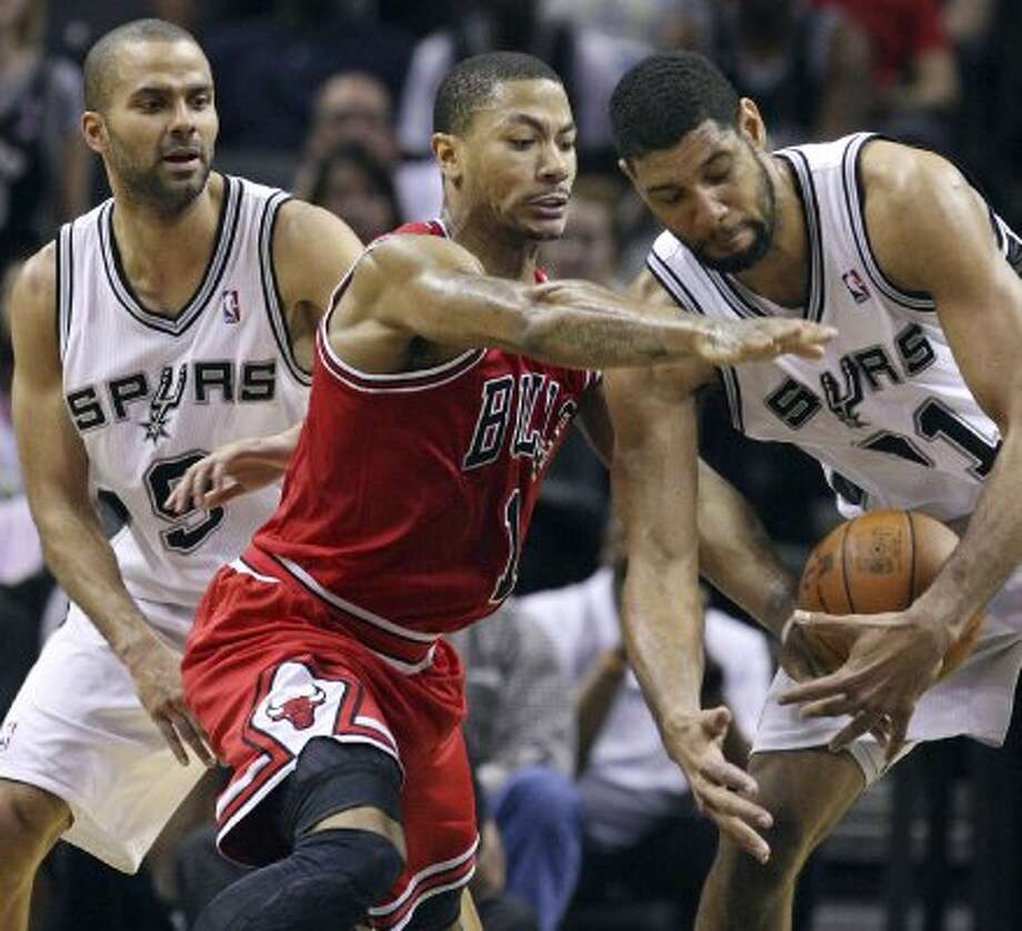 FOR SPORTS -  Chicago Bulls' Derrick Rose and San Antonio Spurs' Tim Duncan grab for a loose ball as San Antonio Spurs' Tony Parker looks on during second half action Wednesday Feb. 29, 2012 at the AT&T Center. The Bulls won 96-89. (PHOTO BY EDWARD A. ORNELAS/SAN ANTONIO EXPRESS-NEWS) (SAN ANTONIO EXPRESS-NEWS)