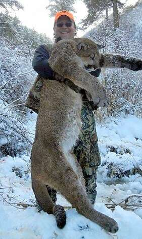 Fish and Game Commission President Daniel Richards holds the cougar he killed. Photo: Courtesy WONews.com