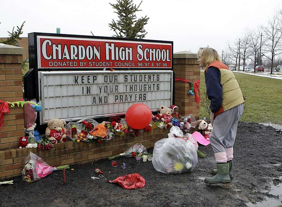 Helga Davies pauses after placing a basket of flowers at a memorial in front of Chardon High School in Chardon, Ohio Wednesday, Feb. 29. The Geauga County town 30 miles east of Cleveland is mourning the death of three students and the wounding of two others in a shooting at the high school Monday morning. Photo: Mark Duncan, Associated Press