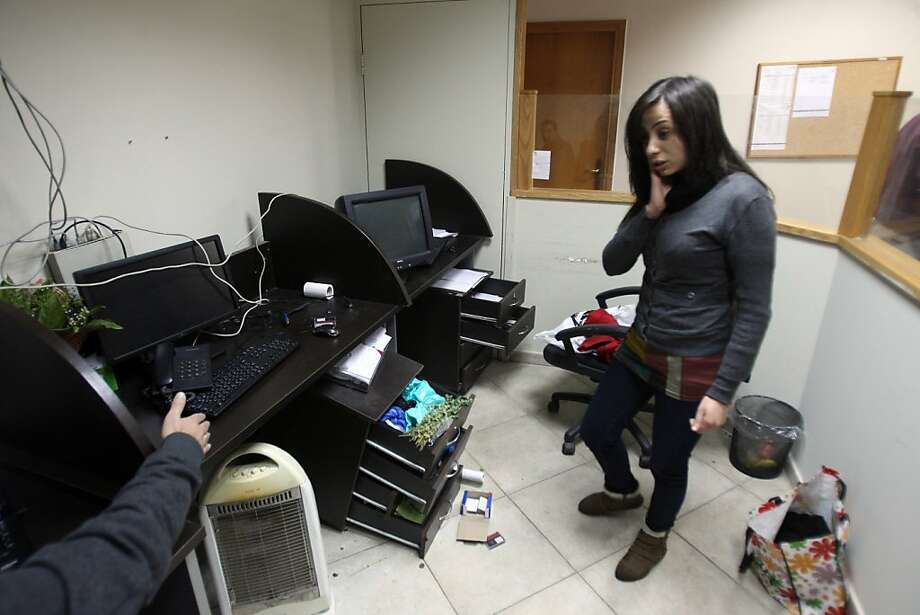 "Staff members of a local private television station ""Watan"", look at the damage caused after Israeli troops raided this and another Palestinian television station in the West Bank city of Ramallah overnight, seizing computers and broadcasting equipment, employees told AFP on February 29, 2012. Photo: Abbas Momani, AFP/Getty Images"