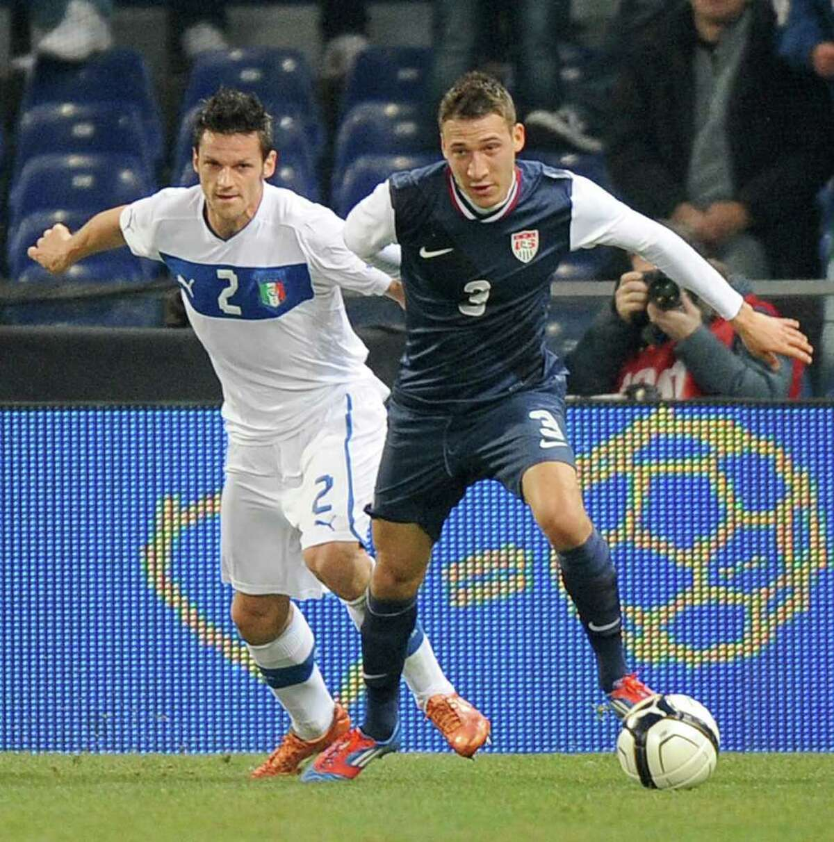 US midfielder Fabian Johnson, right, and Italy midfielder Cristian Maggio vie for the ball during a friendly soccer match between Italy and USA, at the Genoa Luigi Ferraris stadium, Italy, Wednesday, Feb. 29, 2012. USA won 1-0.