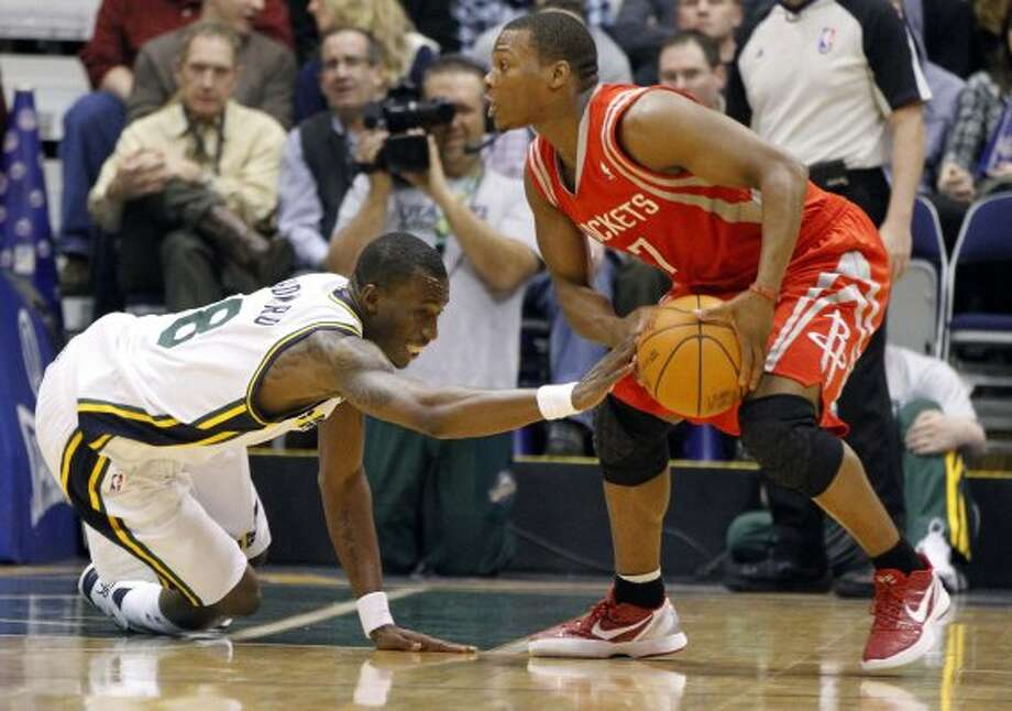 Rockets guard Kyle Lowry grabs a loose ball as Jazz forward Josh Howard scrambles. (Jim Urquhart / Associated Press)
