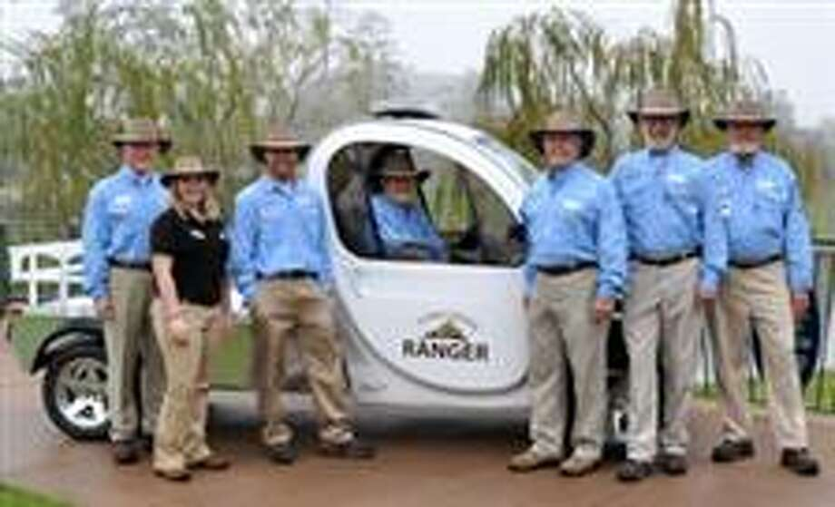 The Woodlands Township Town Center Rangers will use Global Electric Motorcars for transportation around the Town Center area. Rangers are, from left: Ron McPherson, Amber Parsley, Dave Berkley, Jim Nelson, Alberto Ferrer, Jon Krenytzky and Bob Griggs.