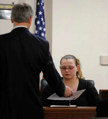 Loretta Colegrove looks over some of the evidence while on the stand during the trial of Matthew Slocum, her boyfriend, in Washington County Court in Fort Edward, N.Y. March 1, 2012.  Slocum is  accused of killing three people in White Creek last year and Colegrove testified that she saw him kill one of the people.  (Skip Dickstein / Times Union) Photo: SKIP DICKSTEIN / 2011