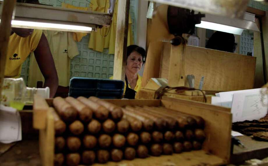 A worker rolls cigars at the Cohiba factory during a press tour as part of the annual Cigar Festival in Havana, Cuba, Thursday March 1, 2012.  Sales of Cuba's famed cigars are hot, despite continued recession fears in Europe, and a U.S. embargo that bars American aficionados from legally lighting up. While Europe remains the top market for such signature Cuban brands as Cohiba, Montecristo, and Romeo y Julieta, sales in Asian nations including China are growing rapidly.  (AP Photo/Javier Galeano) Photo: Javier Galeano, Associated Press / AP
