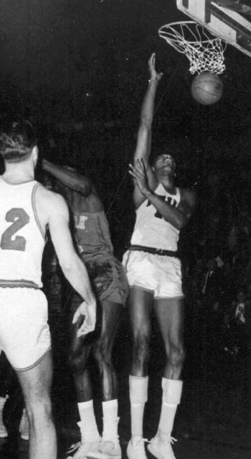 FILE--Philadelphia Warriors' Wilt Chamberlain, right, scores his 100th point, setting an NBA record, during a game against the New York Knicks in Hershey, Pa., March 2, 1962. The ball Chamberlain used to score a record 100 points proved more valuable than anyone expected, it sold at auction Friday, April 28, 2000 for $551,844. Leland's auction house would not say who bought the stolen ball, except to identify him as a ``well-known figure outside the world of sports.'' Photo: AP / AP