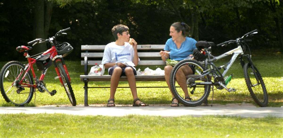 Devin Gund, 13, left and his mom Emabel of Ridgefield rode their bikes to Ballard Park to have lunch on a park bench August 18, 2009