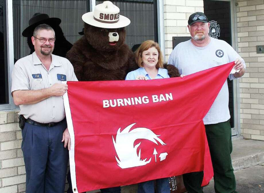 "The Texas Forest Service recently donated ""Burn Ban Flags"" to all local fire departments to help make the public aware when a burn ban has been issued in Hardin County. Pictured; from left, Kountze Fire Chief Jeff Lacomb, Smokey the Bear, Hardin County Emergency Management Coordinator Theresa Wigley, Texas Forest Service District Fire Coordinator Morris Nelms. Photo: David Lisenby, HCN_Flags"