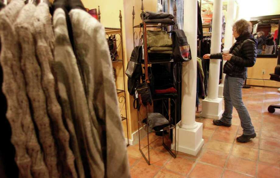 In this Feb. 28, 2012 photo, Laurie Hanson looks over clothing at the Adorn clothing store in Montpelier, Vt. Consumers earned a little more in January and spent most of the extra money. The gains should keep the economy growing at a modest pace. (AP Photo/Toby Talbot) Photo: Toby Talbot / AP