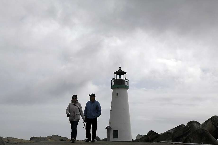 Visitors walk next to a lighthouse under cloudy skies Wednesday, Feb. 29, 2012 at Seabright State Beach in Santa Cruz, Calif. Photo: Marcio Jose Sanchez, Associated Press