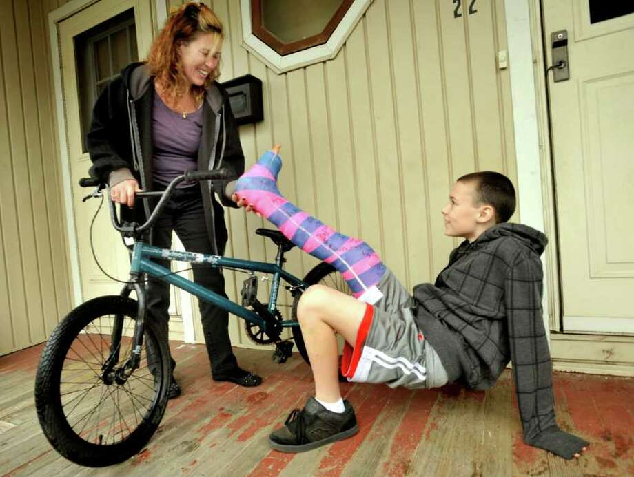 Alex Davis, 11, shows his mom, Barbara Davis Blanchard, that although his leg is broken after being hit by a car on his bike, he can still lift it. Photographed outside their New Milford home Thursday, March 1, 2012. Photo: Michael Duffy / The News-Times