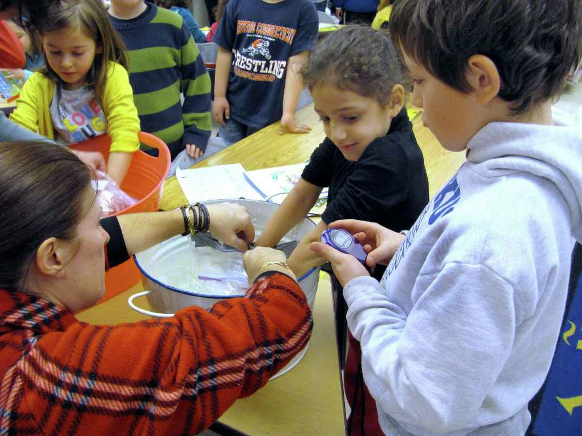 From left, Ruth Dyer, Keila DoNascimento and Henry Barrios work on an experiment at last at theWestern Connecticut Academy for International Studies in Danbury. The children were studying the continent of Antarctica. Students in kindergarten and grade 2 learn about animal adaptations. Partner teams investigated how long it took to feel the cold of the water with their hands using plastic bags filled with fat ( vegetable shortening) and those containing nothing.