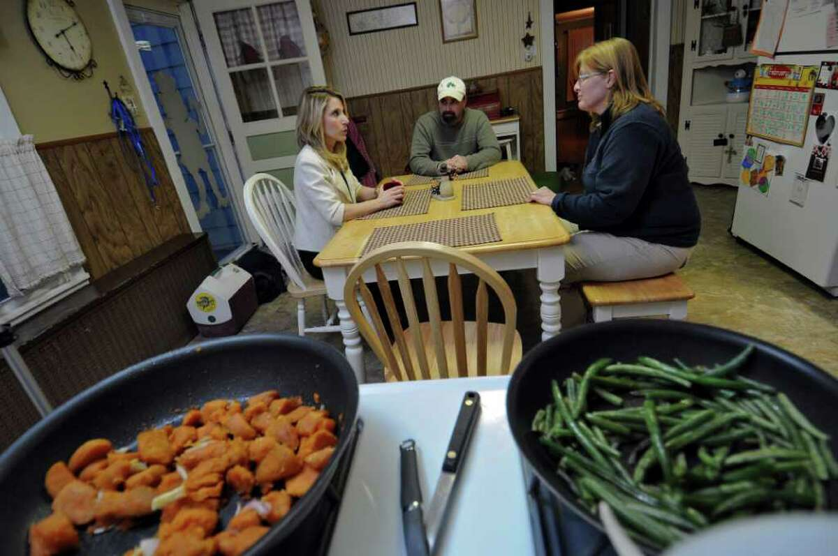 Stephanie DiBacco, a dietician at Russell Sage College, left, visits with Darrin and Vanessa Gleason at their home on Wednesday evening Feb. 22, 2012 in Waterford, NY. (Philip Kamrass / Times Union )