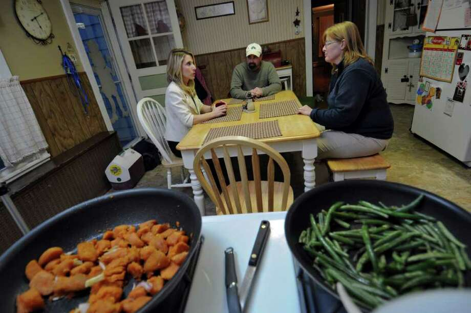 Stephanie DiBacco, a dietician at Russell Sage College, left, visits with Darrin and Vanessa Gleason at their home on Wednesday evening Feb. 22, 2012 in Waterford, NY. (Philip Kamrass / Times Union ) Photo: Philip Kamrass / 00016499A