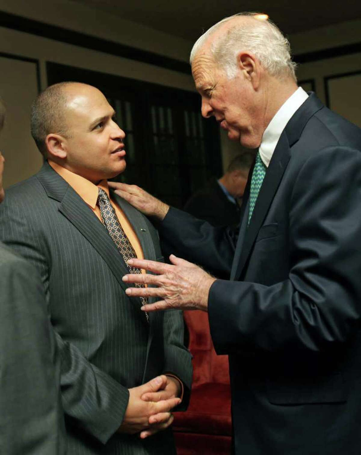 Former Secretary of State James Baker III (right) speaks with Capt. Juan Guerrero before a luncheon to benefit Operation Comfort at the San Antonio Country Club. Wounded troops from SAMMC attended the fundraiser Thursday, March 1, 2012.