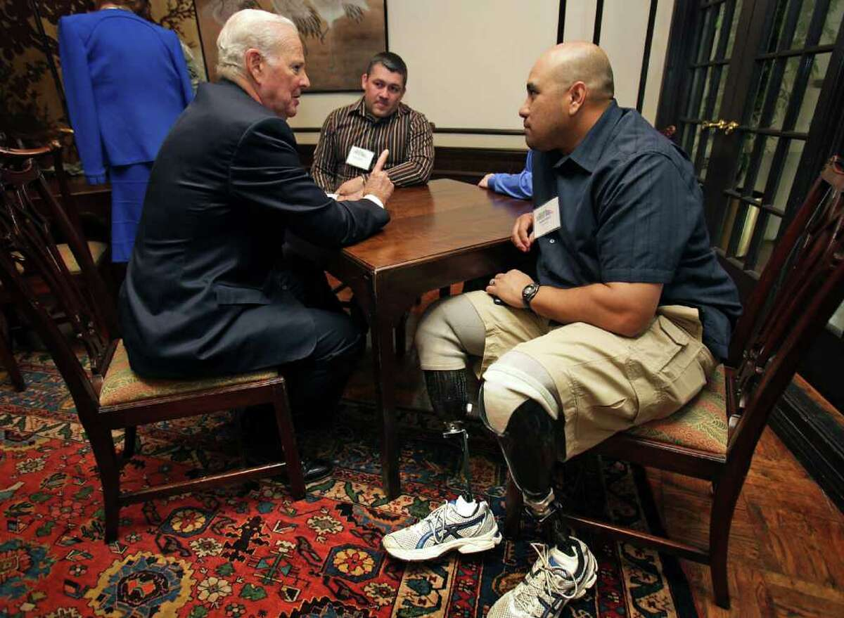 Former Secretary of State James Baker III speaks with Moses Sonera (center) and Daniel Robles before a luncheon to benefit Operation Comfort at the San Antonio Country Club. Wounded troops from SAMMC attended the fundraiser Thursday, March 1, 2012.