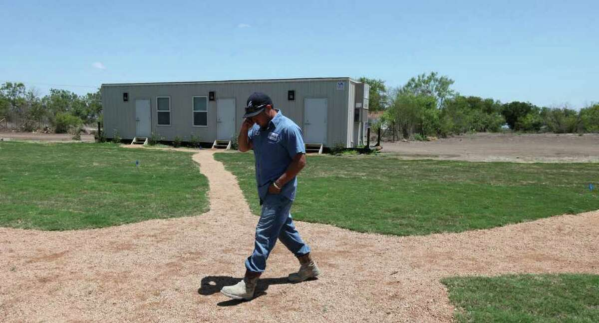 Supreme Services oil field worker Freddy Trevino walks past the Remote Logistics International LLC Three Rivers Lodge last summer. The housing shortage in Three Rivers and the surrounding area is being painted as critical.