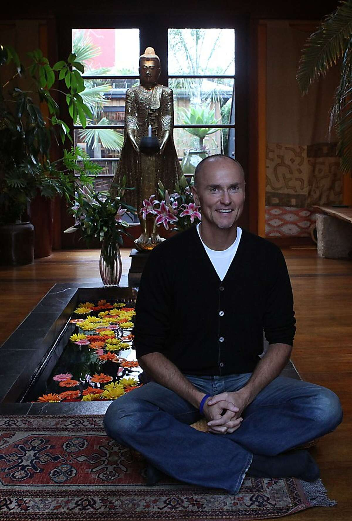 A golden Buddha and a pond with brightly colored daisies, above, more than decoration in Chip Conley's home, that testify to a life of introspection and travel.