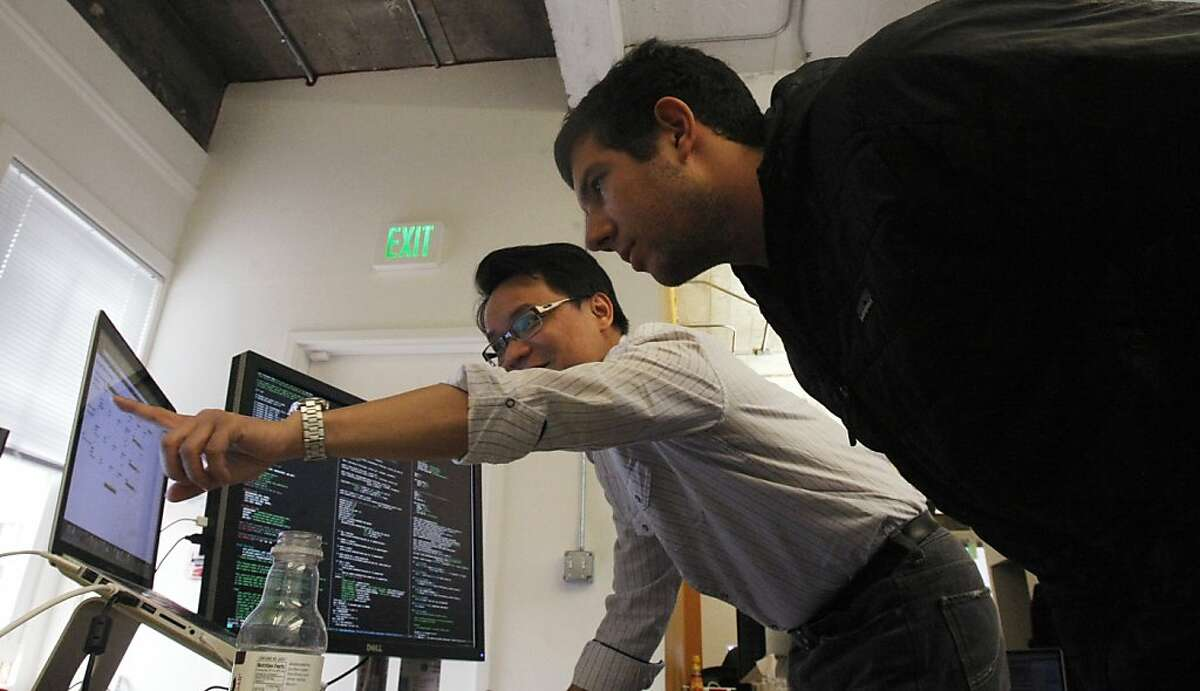 Nextdoor employees Kip Kaehler, a software engineer and Wilson Chan, vice president of finance, discuss a project at the company's headquarters in downtown San Francisco onFebruary 21, 2012.Nextdoor is a private social network that creates connections between people living in different neighborhoods.