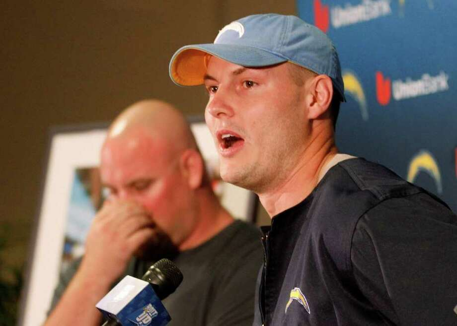San Diego Chargers quarterback Philip Rivers talks about lineman Chris Dielman, rear, during a news conference in which Dielman announced his retirement from NFL football, Thursday, March 1, 2012 in San Diego. Photo: AP