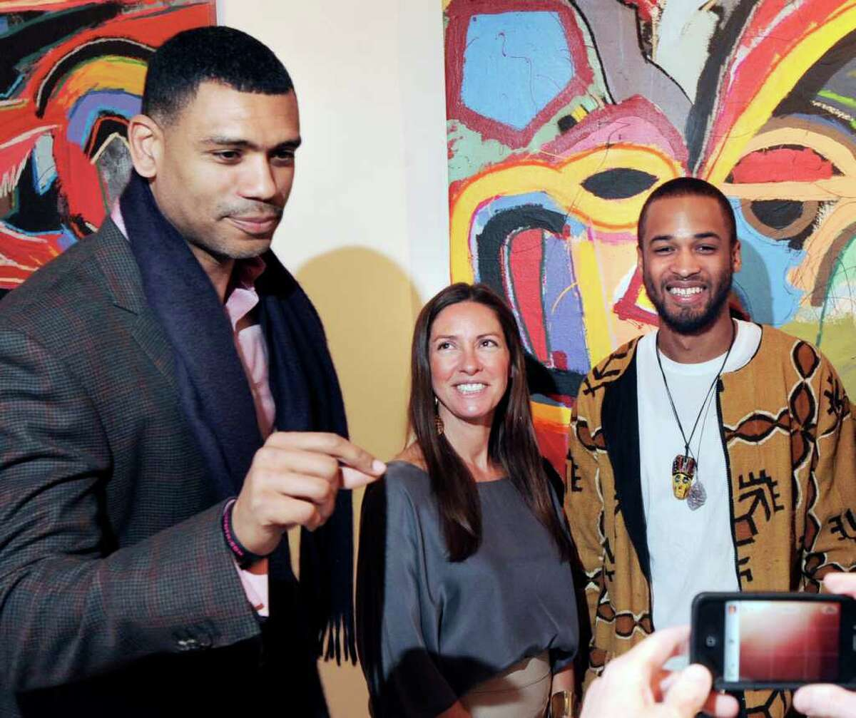 Allan Houston, left, of Greenwich, prepares to get his photo taken with his nephew, artist, Asa Jackson, right, and gallery owner, Cindy Milazzo, center, at the Samuel Owen Gallery in Greenwich Thursday night, March 1, 2012. Jackson was having a solo exhibtion of his work at the gallery.