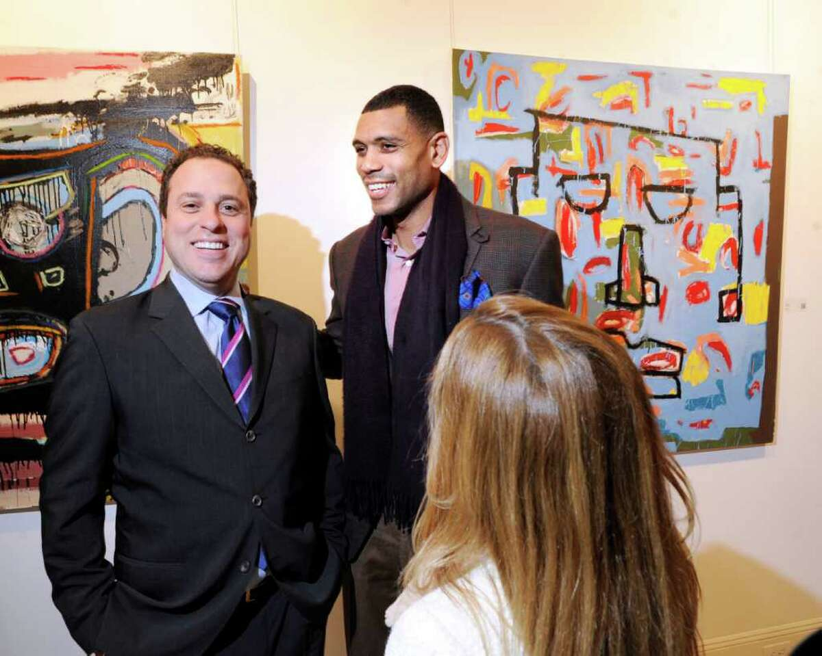 Lloyd Mandell, left, of Greenwich with Allan Houston, right, also of Greenwich, during an opening reception for Houston's nephew Asa Jackson at the Samuel Owen Gallery in Greenwich Thursday night, March 1, 2012.