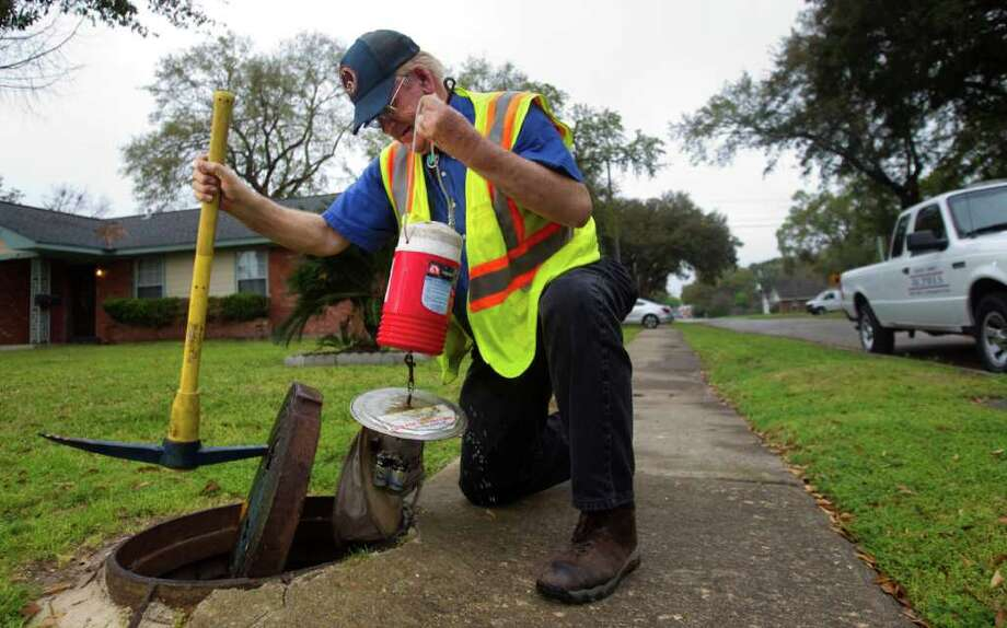 Bill Grieneeks, of the Harris County Public Health and Environmental Services Mosquito Control Division, pulls a mosquito trap from a manhole on Thursday. Photo: Brett Coomer / © 2012 Houston Chronicle
