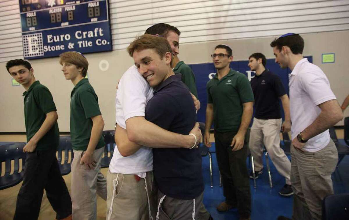 Co-Captains Isaac Buchine and Isaac Mirwis embrace each other after a press conference at Beren Academy where the boys basketball teams will be allowed to play in the state semifinal game. The game is today.