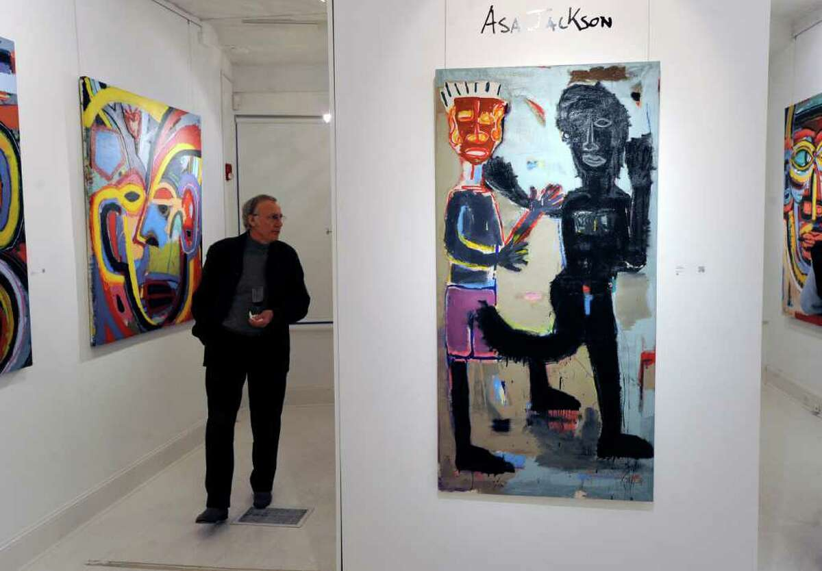 Tony Gorman of Stamford views works by artist Asa Jackson during an opening reception at the Samuel Owen Gallery in Greenwich Thursday night, March 1, 2012.