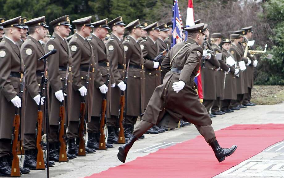 A member of the Croatian honor guards jumps over the red carped before the arrival ceremony for Austria's President Heinz Fischer, in Zagreb, Croatia, Thursday, March 1, 2012. President Fischer is on and official visit to Croatia. (AP Photo/Darko Bandic) Photo: Darko Bandic, Associated Press