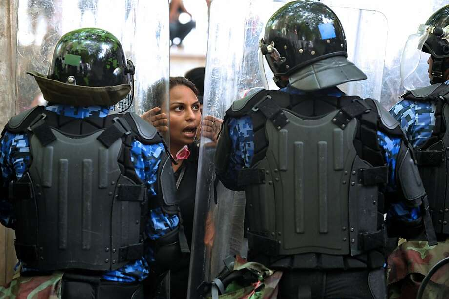 Maldivian policemen stand guard as a protestor shouts slogans during a rally in Male on March 1, 2012.  Opposition MPs in the Maldives have prevented the new president, who is accused of seizing power in a coup, from opening parliament as violent protests erupted outside the building. Opposition lawmakers grabbed the Speaker's chair amid angry scuffles, according to local reports, and stopped President Mohamed Waheed from addressing the assembly in the capital Male. Police said 14 officers were wounded, four of them seriously, in clashes with opposition demonstrators around the parliament. At least 34 people were also arrested. Photo: Ibrahim Faid, AFP/Getty Images