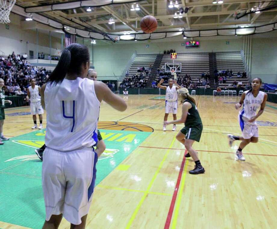 Emia Willingham-Hurst, of the Albany Lady Falcons, passes the ball from the sidelines to team mate Crystal Mallet at the Class AA girls' semifinals between Albany High School and Shenendehowa High School at Hudson Valley Community College, Troy, on Thursday, March 1, 2012. (Erin Colligan / Special To The Times Union)